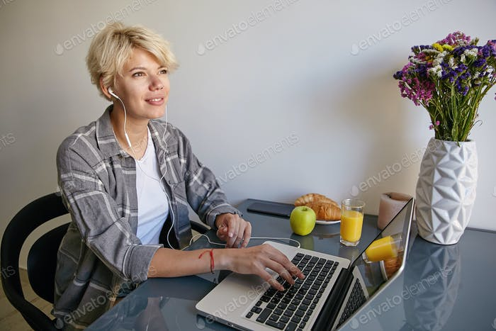 Indoor portrait of lovely young female in casual clothes sitting next to laptop with headphones