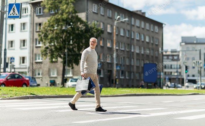 senior man with shopping bags walking on crosswalk