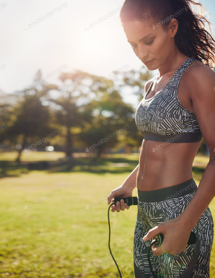 Fitness woman with jump rope in a park