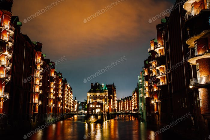 Hamburg, Germany. View of Wandrahmsfleet at dusk illumination light with clouds above. Located in