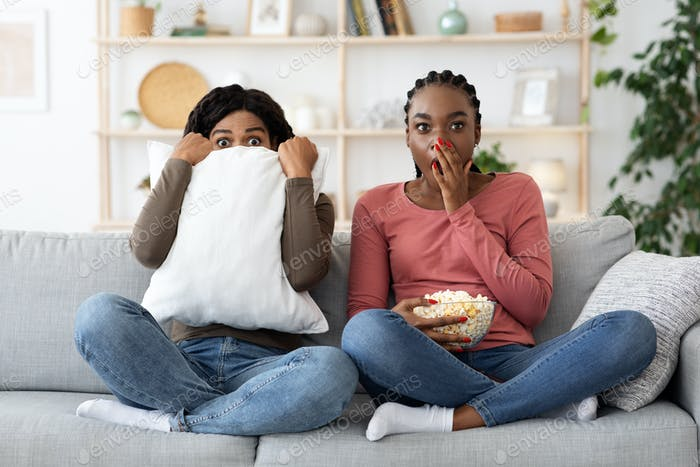 Frightened black girlfriends watching horror together at home