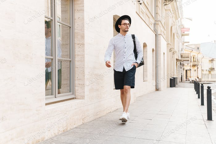 Photo of handsome unshaven man looking aside while walking in city street