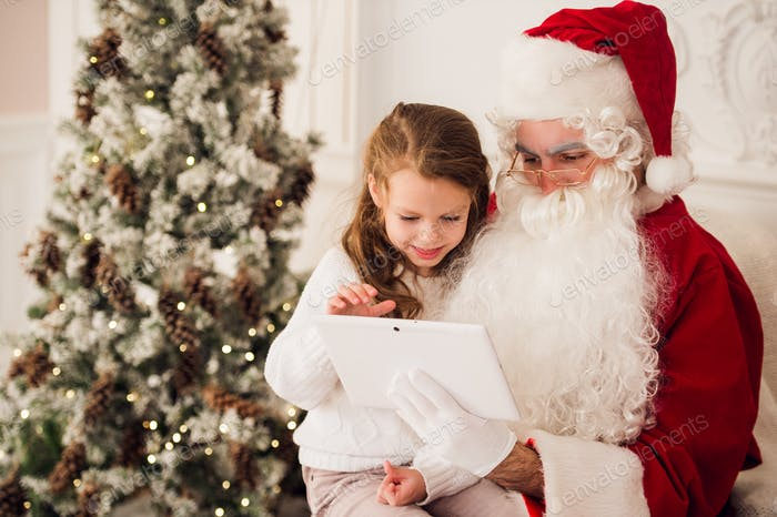 Kleines Mädchen sitzt mit Santa mit Tablet auf dem Sessel zu Hause Wohnzimmer