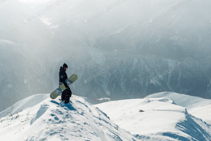 man stay and watch with snowboard equipment