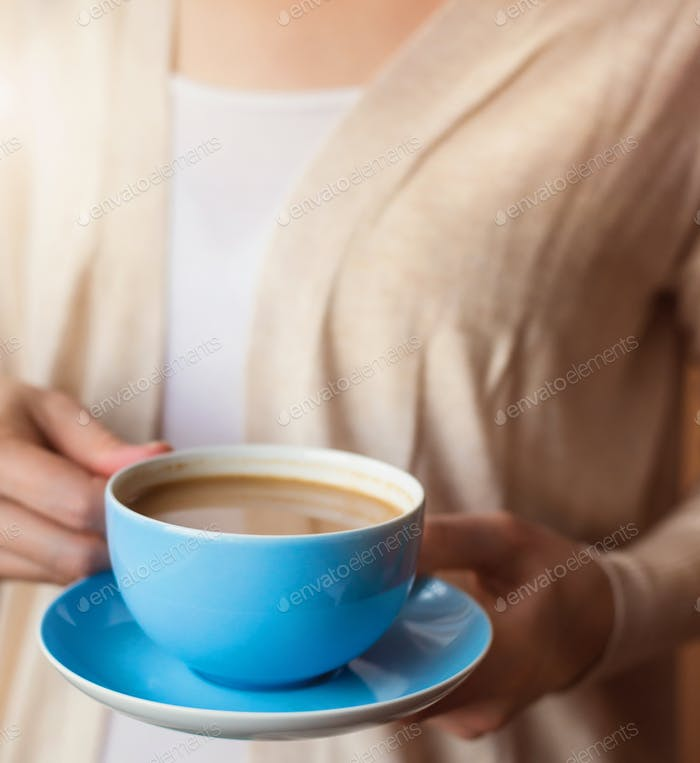 Unrecognizable woman with cup of coffee