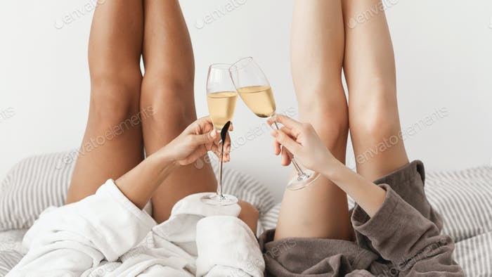 Ladies with naked legs toasting with champagne glasses
