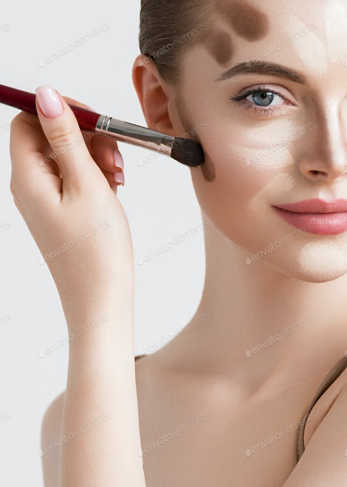 Makeup woman face cosmetic applying beauty concept. Beige background.