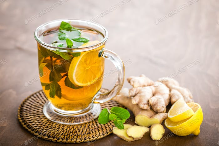 Hot herbal tea with fresh lemon, ginger and mint leaves on brown background, closeup