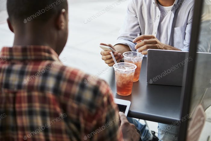 Crop shot of two male friends with cold drinks outside cafe