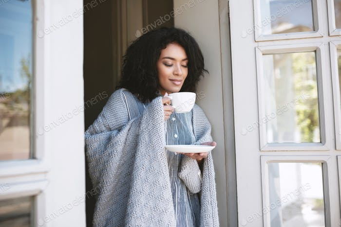 Young girl standing with cup of coffee and dreamily closed her eyes