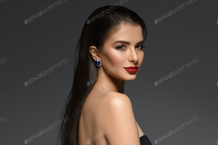Schöne Frau mit langen Brünette glatte Schönheit Haar über dunklen Hintergrund. Weiblich