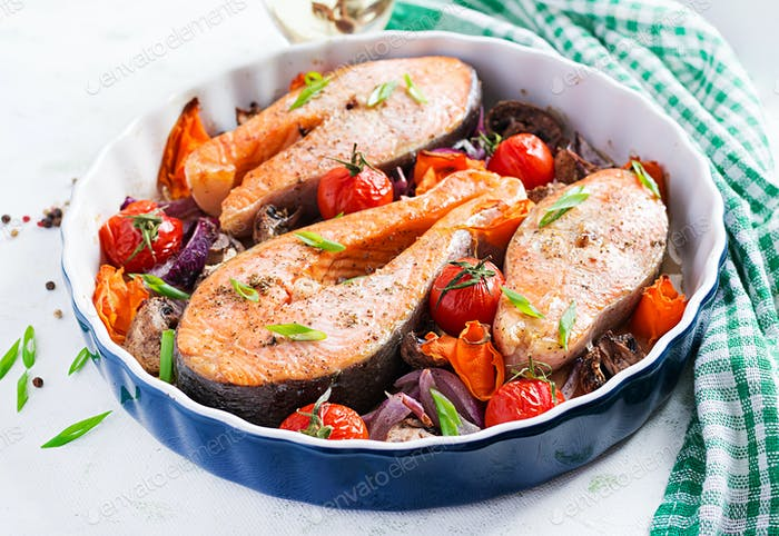 Ketogenic dinner. Baked salmon fish steak with tomatoes, mushrooms and red onions.