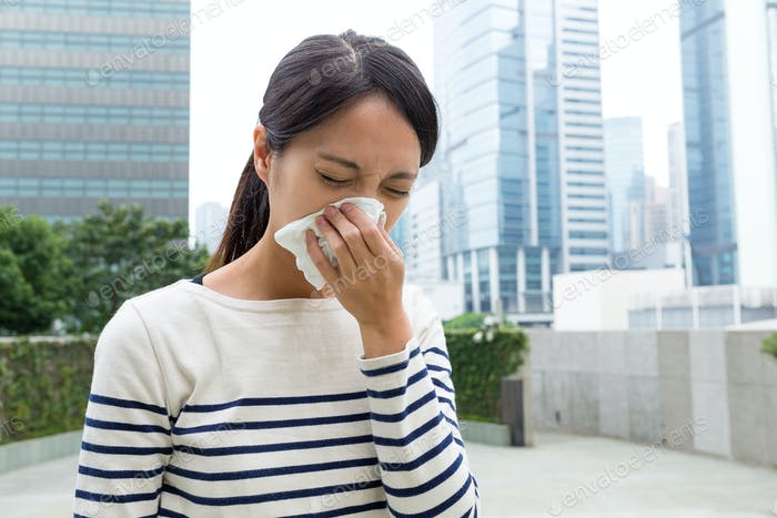 Woman suffer from sneezing at outdoor