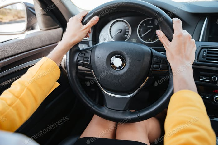 Manos sosteniendo la rueda del coche y la conducción