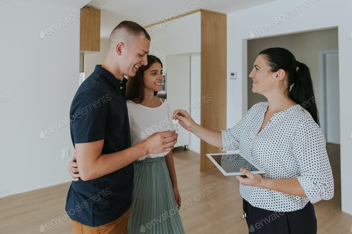 Estate agent handing keys to young couple in new house.