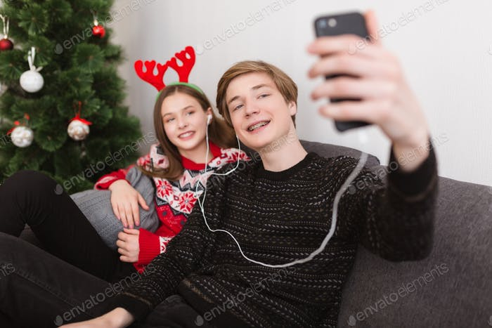 Young couple on sofa at home in earphones and taking selfie with Christmas tree on background