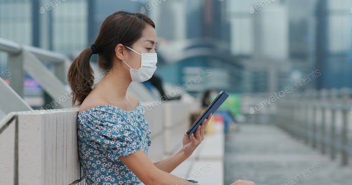 Woman wear face mask and use of mobile phone in city