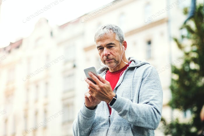 A portrait of an active mature man standing outdoors in city, using smartphone.