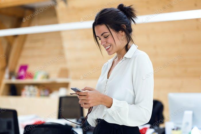 Smiling young businesswoman texting with mobile phone on coworki