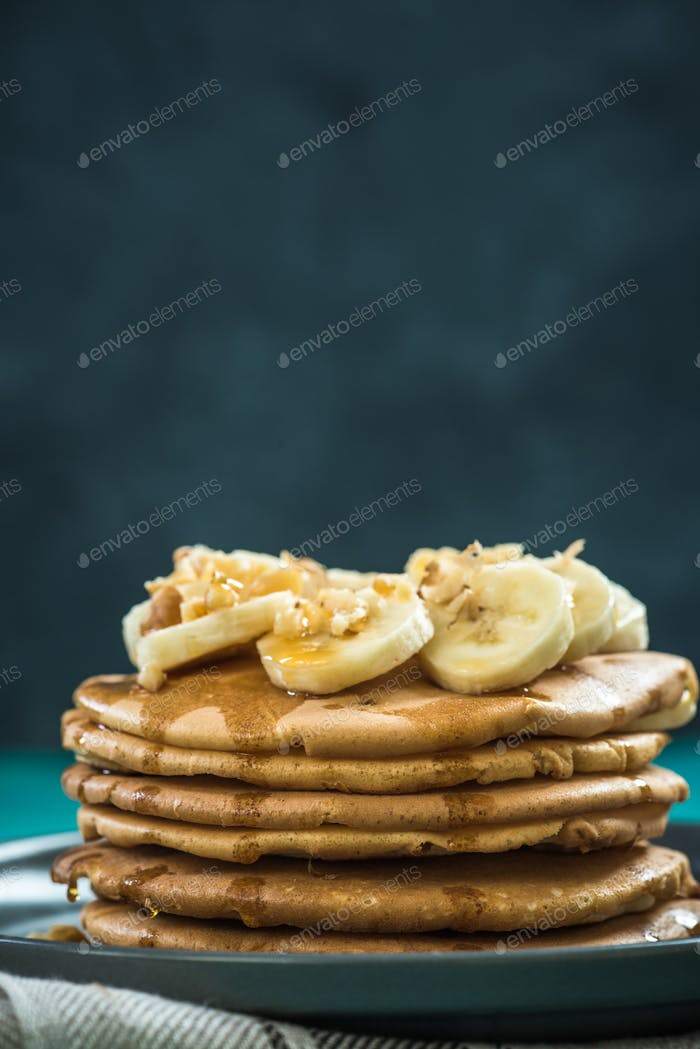 Pancakes topped with fresh banana and walnuts.