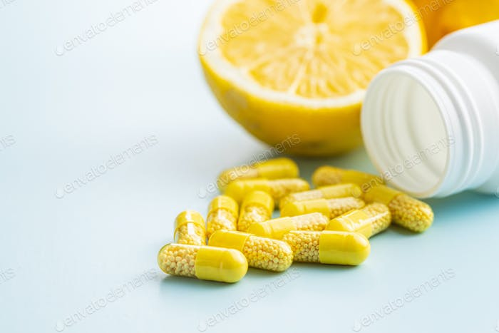 Vitamin capsules. Vitamin C pills, lemon fruit and pill bottle.