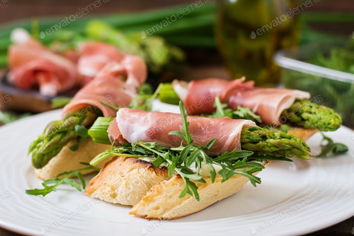 Toasts (sandwich) with asparagus, arugula and prosciutto