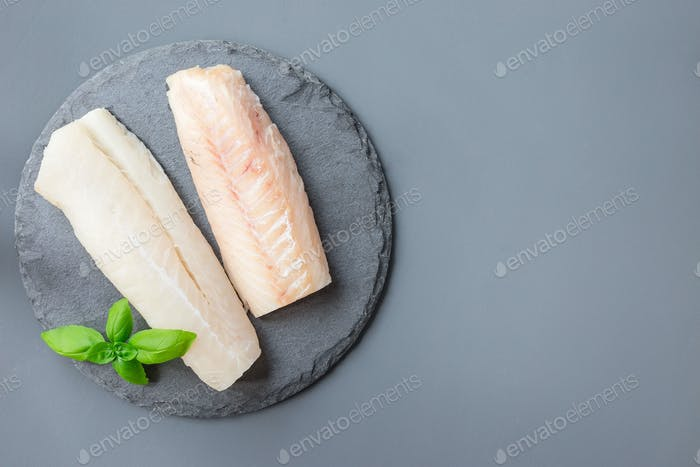 Fresh raw cod fillet with basil on stone plate, horizontal, copy