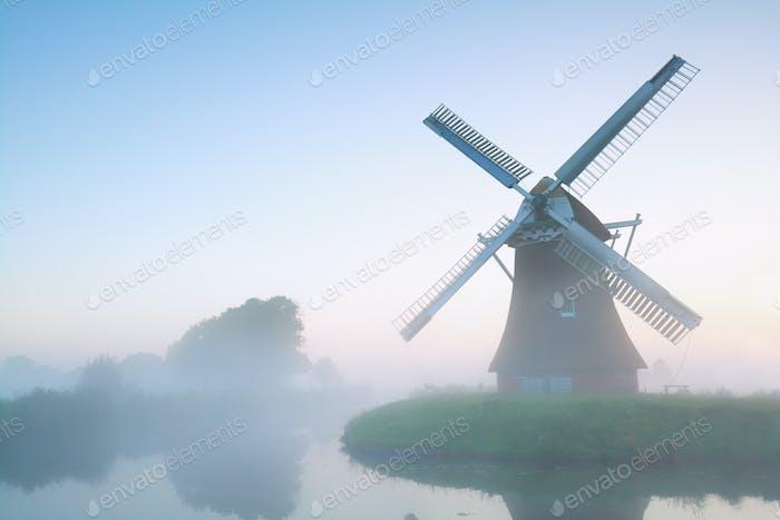molino de viento encantador en la niebla de la mañana