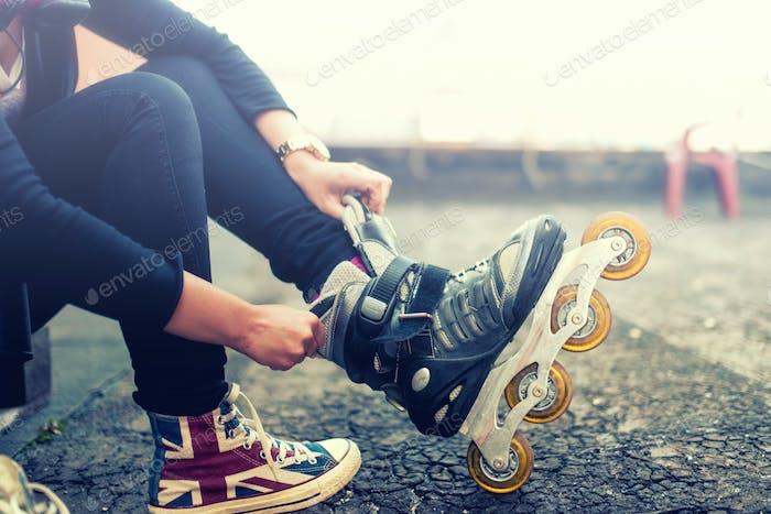 chica disfrutando del patinaje sobre ruedas, poniéndose en patines después de las actividades. Efecto Vintage.