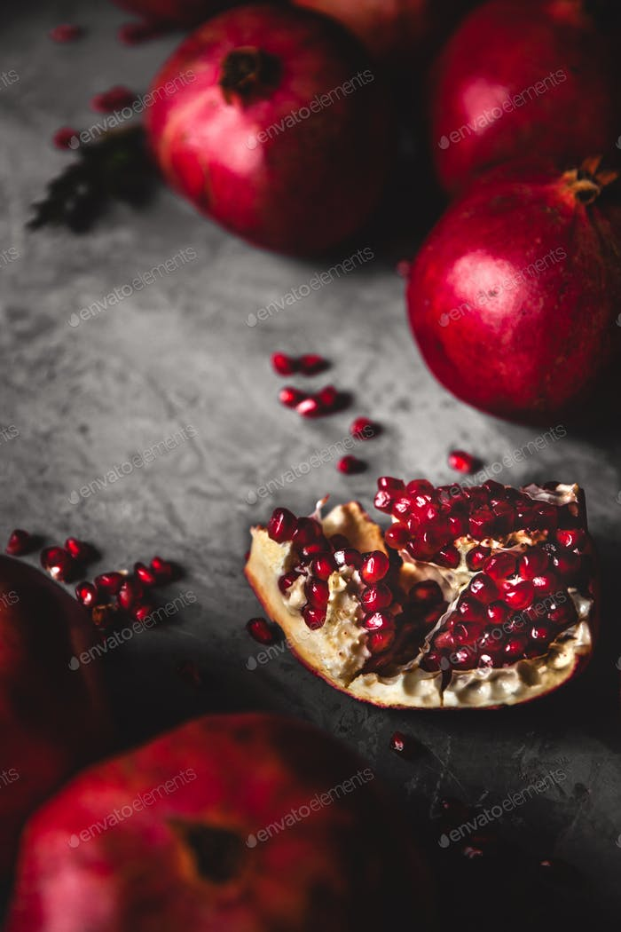 Pomegranate fruit. Ripe and juicy pomegranate on rustic grey background with copy space