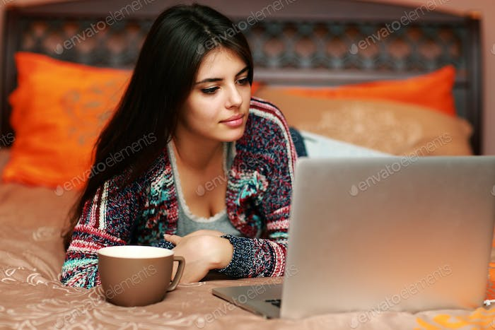 Beautiful woman lying on the bed with cup of coffee and looking at laptop
