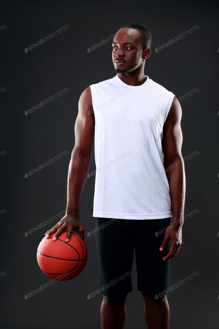 portrait of african american man holding basketball ball photo by