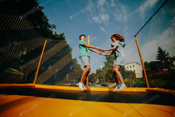 Couple jumping on trampoline in the park