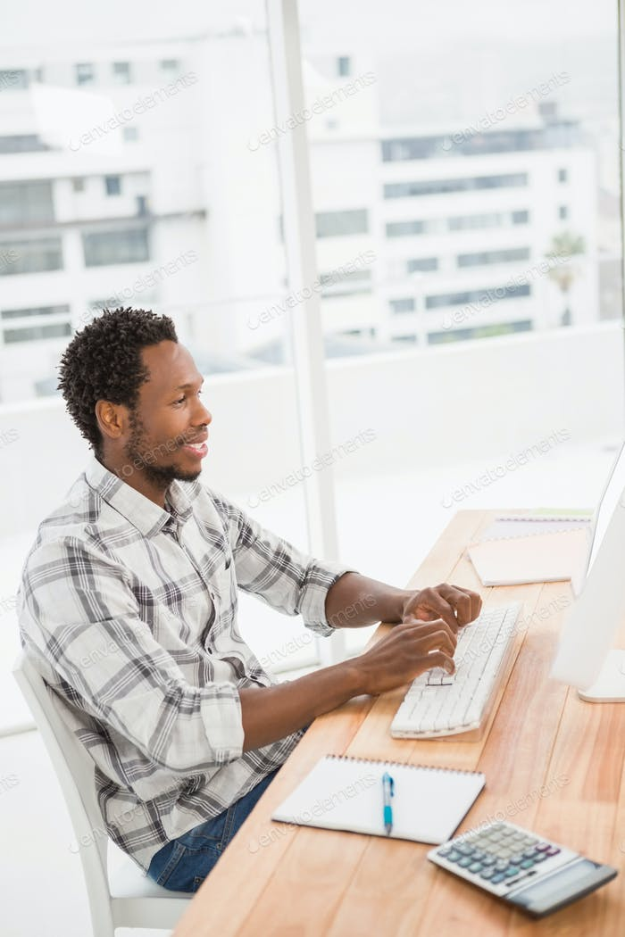 Young businessman sitting at his desk and writing on the computer in the office