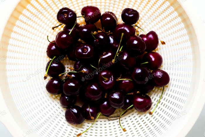 Berries of a sweet cherry in a colander on a white background