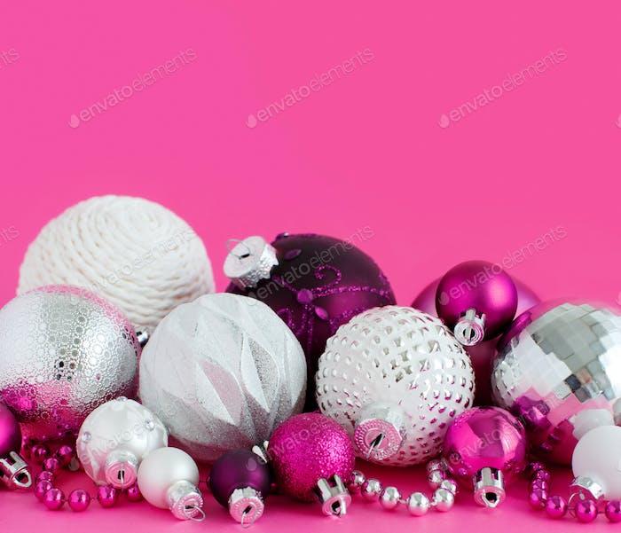 Weihnachtskugeln auf rosa Hintergrund
