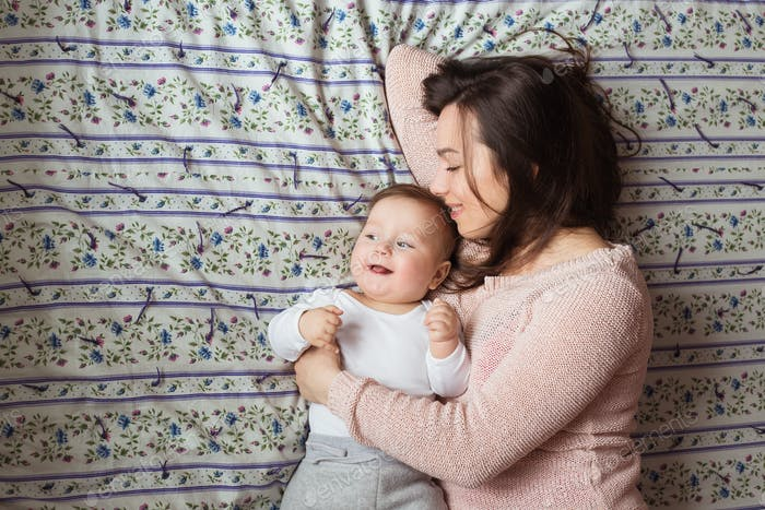 Eine Mutter und ein kleines Kind auf einem Bett.