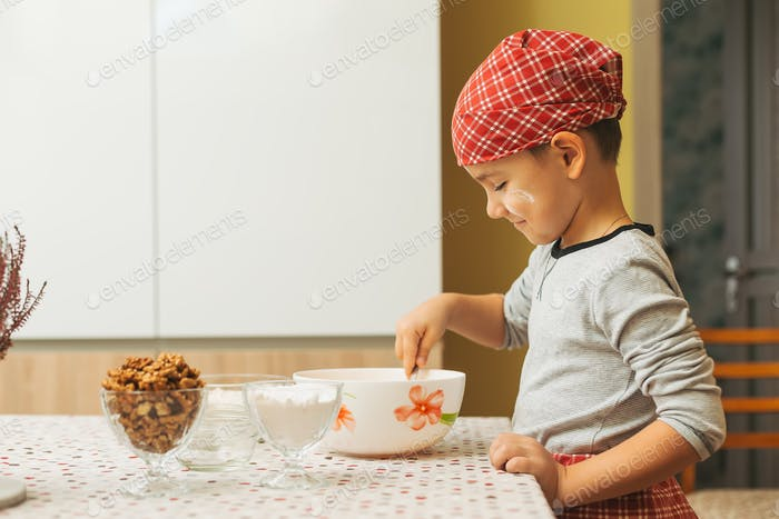 Profile boy is cooking in a luminous kitchen mixing ingredients