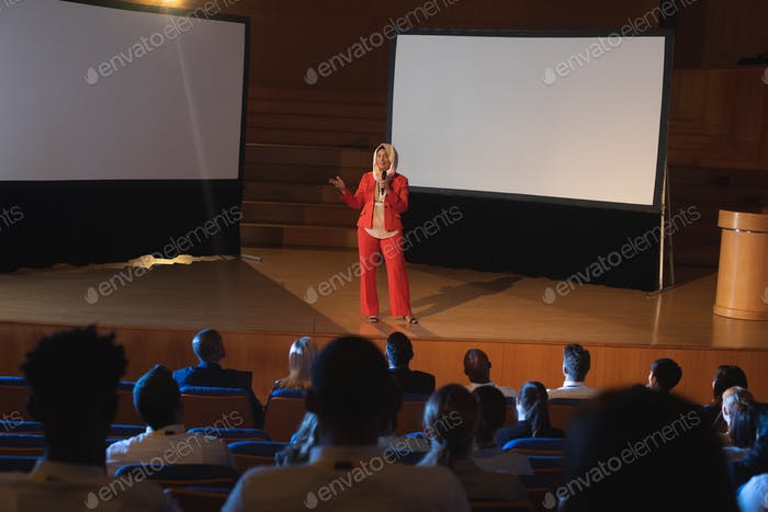 Businesswoman standing and giving presentation in auditorium