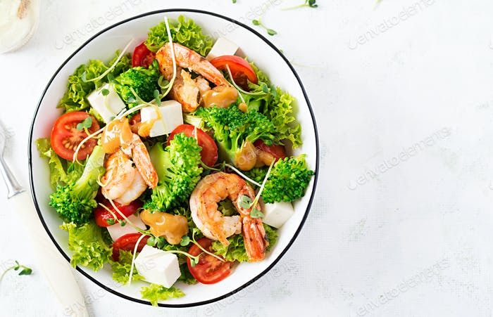 Delicious fresh salad with shrimps / prawns, broccoli, feta cheese, tomatoes, lettuce