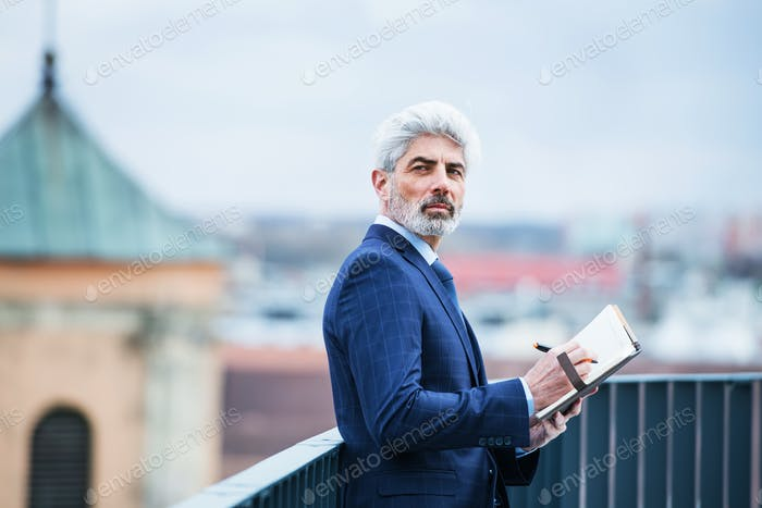 A mature businessman with diary standing on a terrace, writing.
