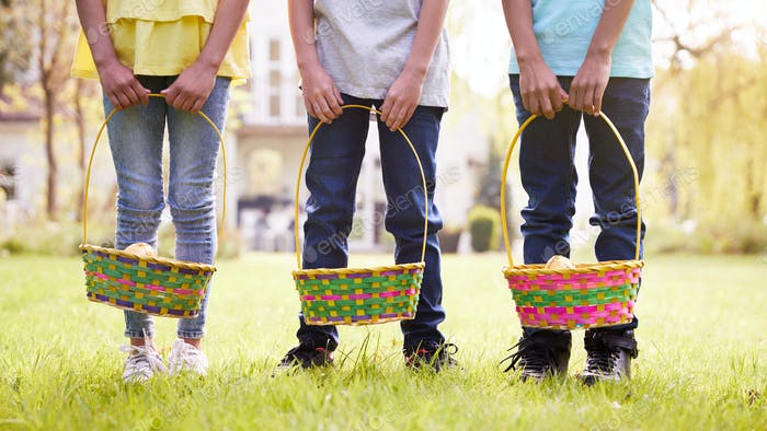 Close Up Of Three Children Holding Baskets On Easter Egg Hunt In Garden