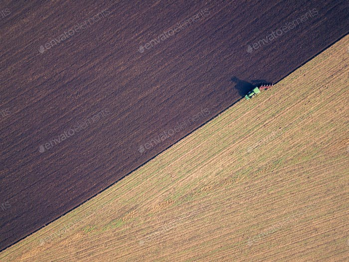 Aerial photo of a tractor ploughing a field in a countryside