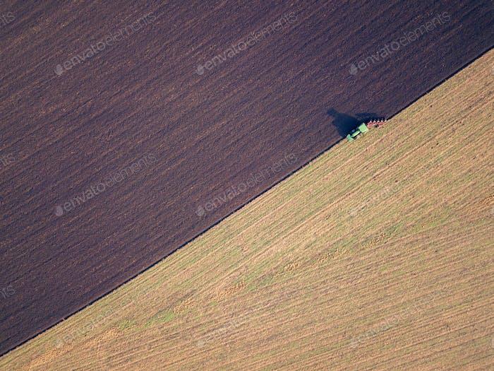 Luftaufnahme eines Traktors, der ein Feld in einer Landschaft pflügt