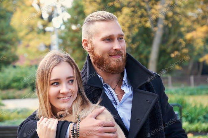 Redhead bearded male hugging cute blonde female.