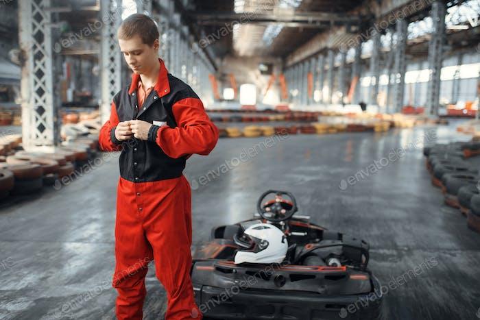 Racer puts on uniform, go kart car on background