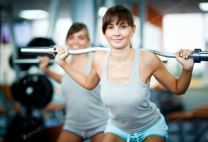 Young smiling brunette woman instructor in grey sportswear showing how to make barbell squat to
