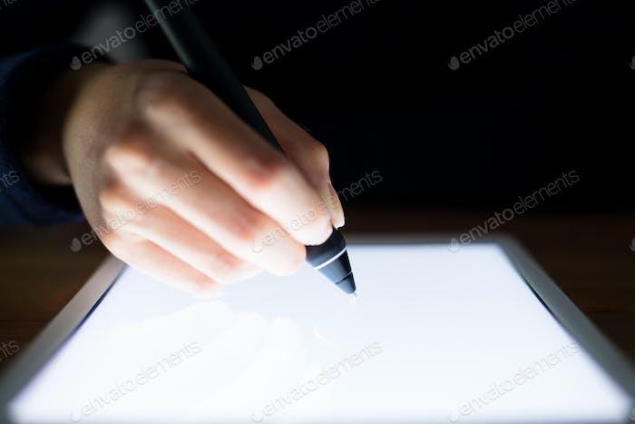 Mujer uso de la pluma para escribir en la tableta pc