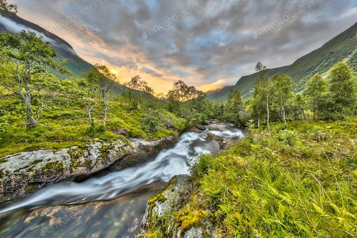 Sonnenuntergang über kleinem Fluss durch Birkenwald in Norwegen