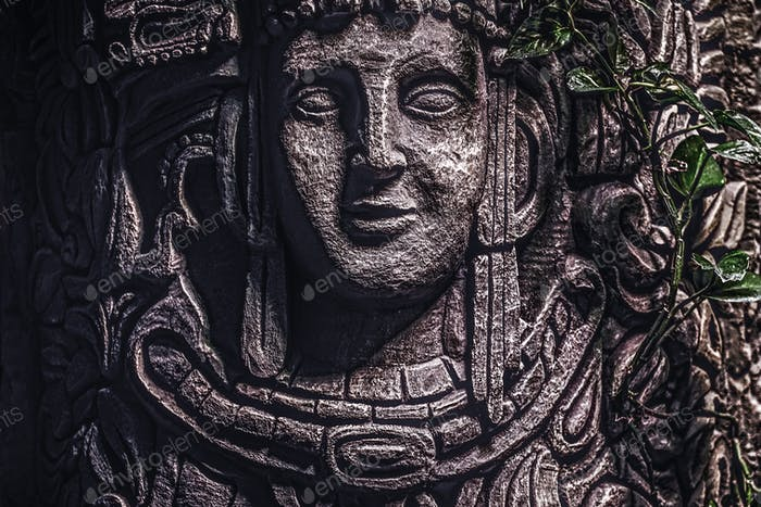 Beautiful rocky monument with a carved image of a human face in the jungle